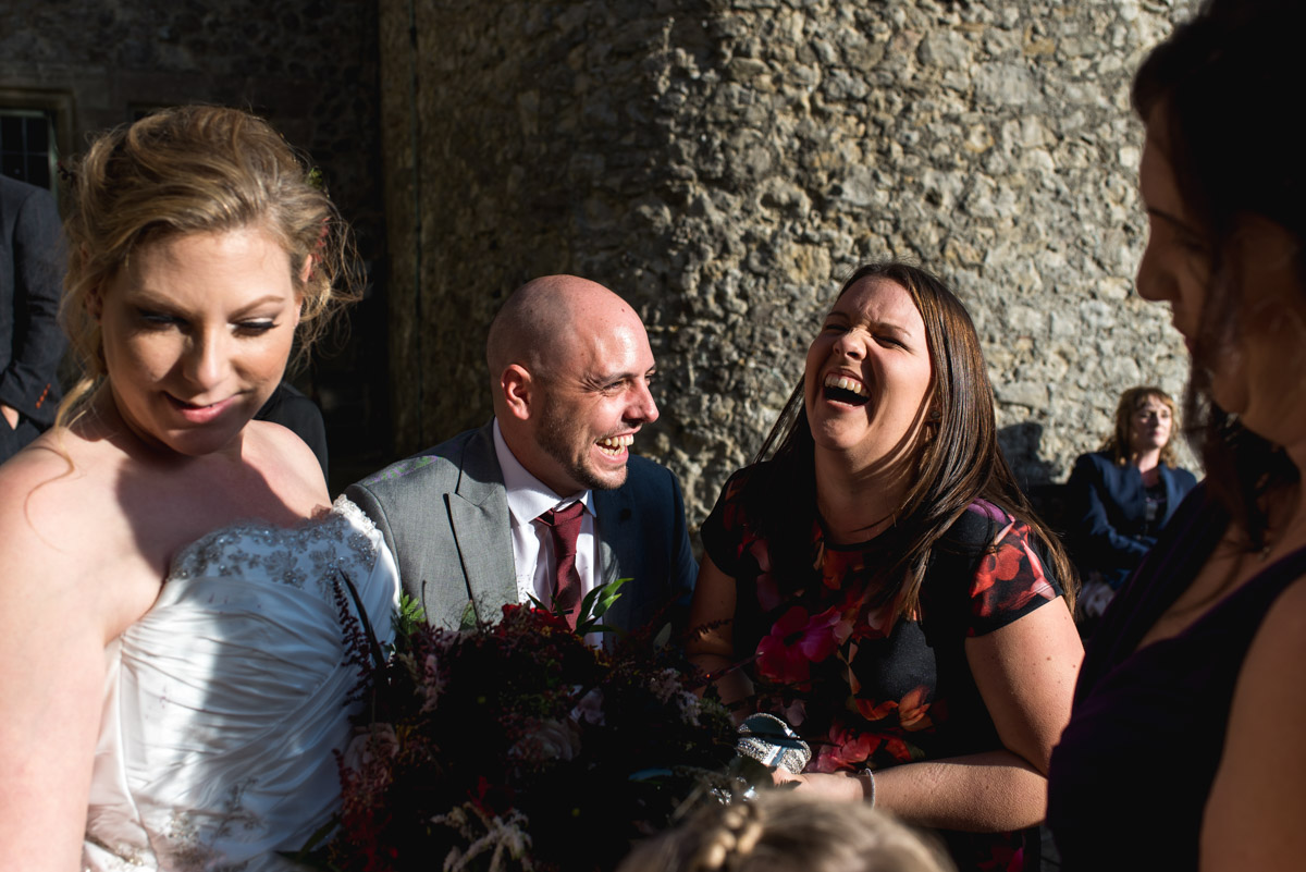 Photograph of guests enjoying a laugh outside in the grounds at Lympne Castle on Lianne and Johns wedding day