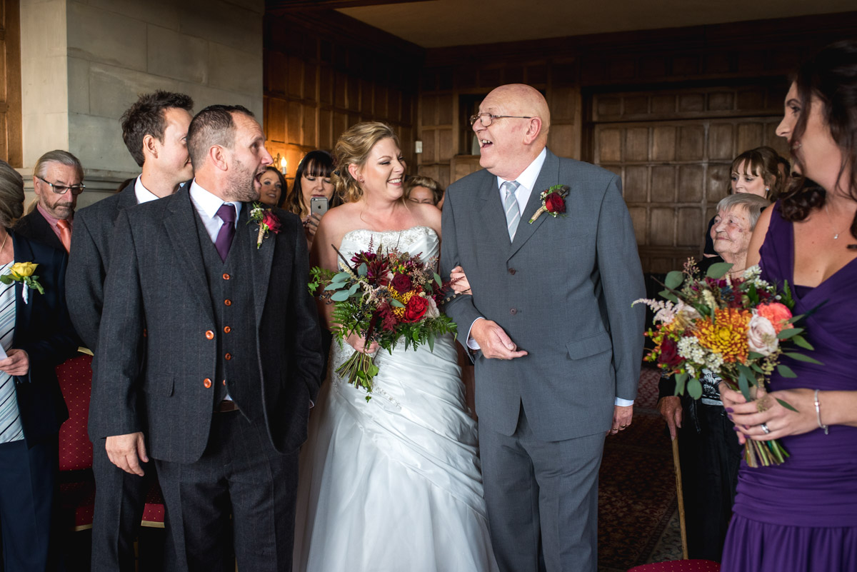 Photograph of Lianne being walked down the aisle at Lympne Castle in Kent for her wedding ceremony